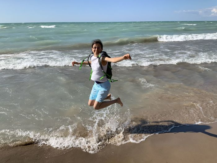 Full length of woman jumping on beach