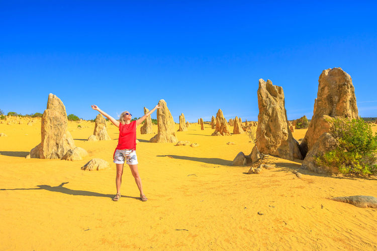 Woman with arms outstretched standing by rock formation against sky