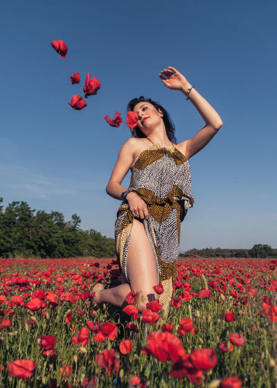Woman with red flowers on field against sky