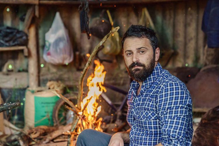 Portrait of man sitting by fire