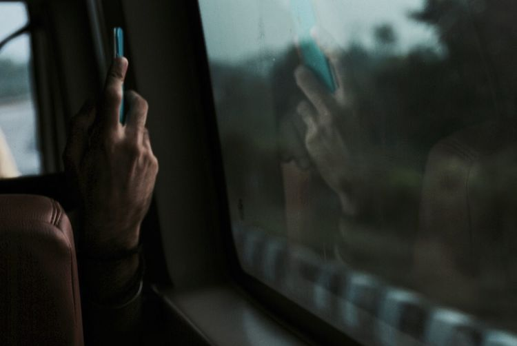 Cropped hand of man photographing by train window with mobile phone