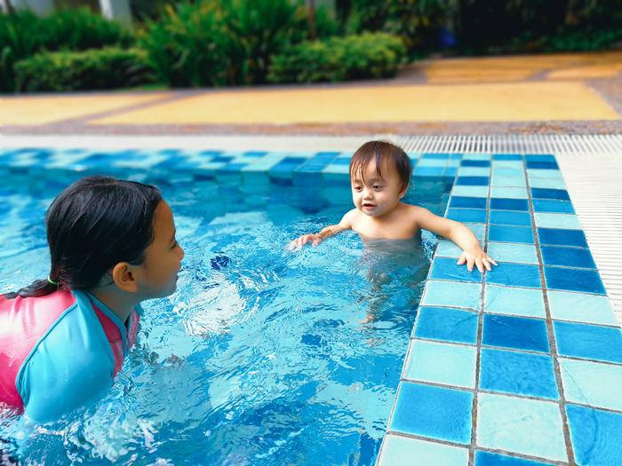 Siblings swimming in pool