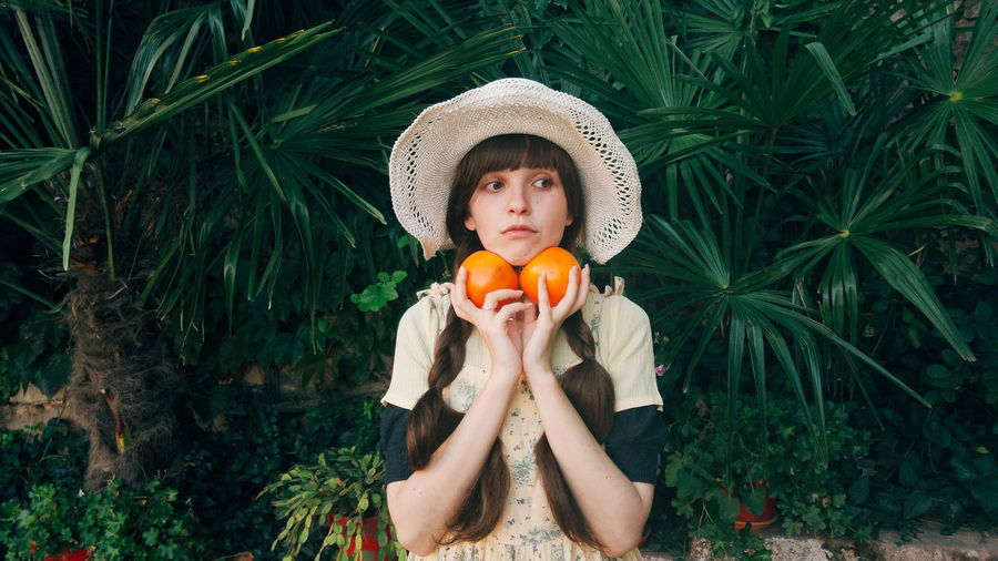Beautiful Woman Citrus Fruit Clothing Day Food Food And Drink Freshness Front View Fruit Hairstyle Hat Healthy Eating Holding Leaf Looking At Camera Nature One Person Orange Plant Plant Part Portrait Wellbeing
