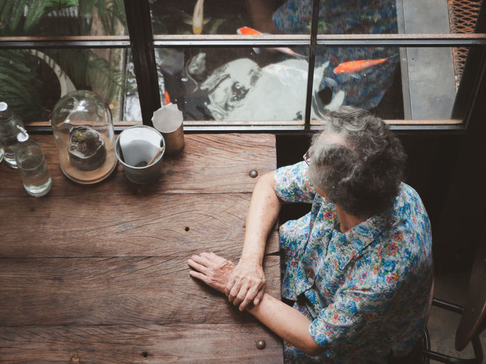Senior woman looking away out of windows while sitting on chair in a cafe shop.