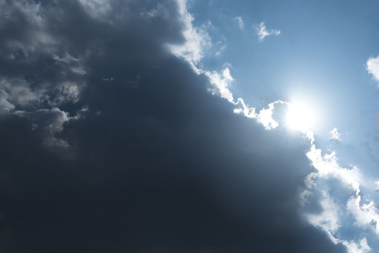 Low angle view of sunlight streaming through clouds