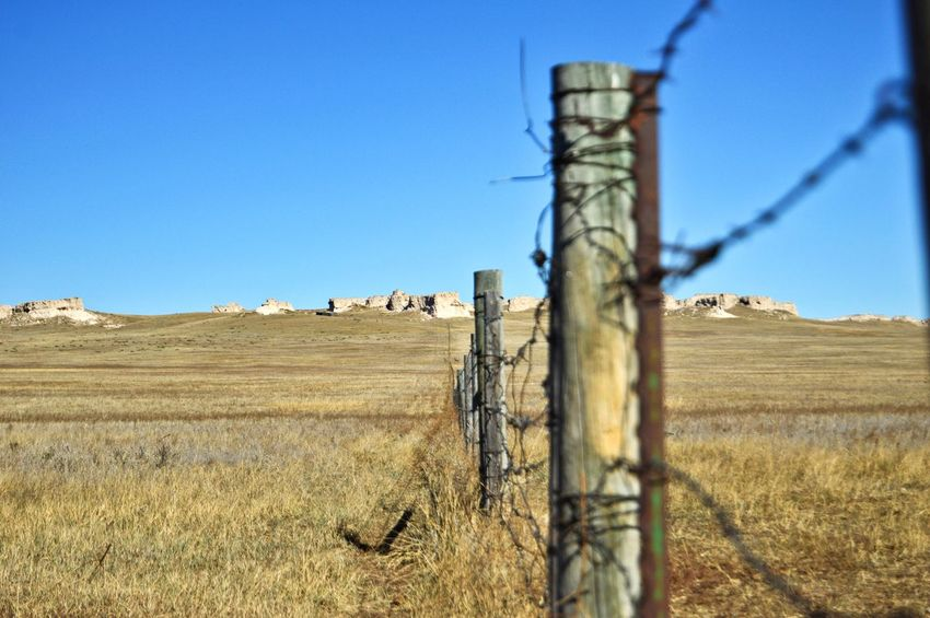 Miles of fence line South Of Lusk Wyoming Wide Open Spaces Outdoors Shadows Rock Formation Grass Pasture Horizon Over Land Clear Sky Rural Scene Wooden Post Blue Barbed Wire Sunlight Wood - Material