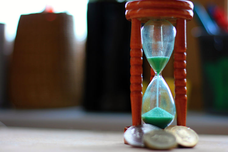 Time is money, don't waste it, make it worth it. An hourglass with falling sand and coins at its feet to underline the importance and val... Composition Desk Hour Motivation Objects Wood Blurred Background Close-up Coin Coins Coins On The Table Day Focus On Foreground Glass Hourglass Indoors  Money No People Sand Space Speed Table Time Time To Reflect Wood - Material