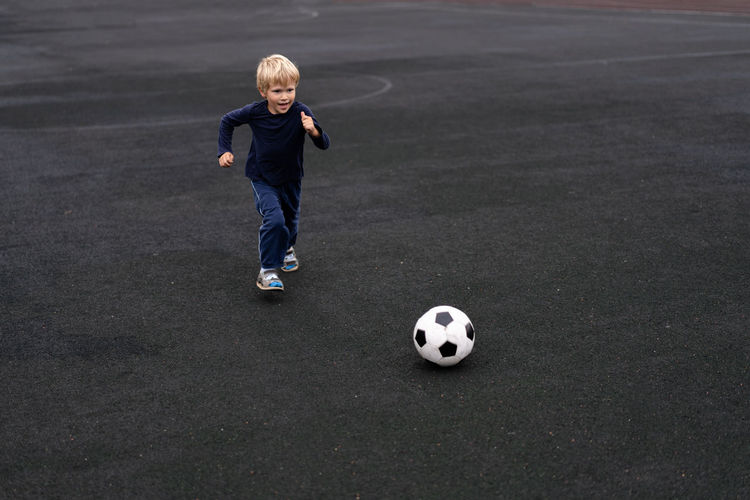 little boy play in football Football Fun Happiness Happy Lifestyle Running Winning Active Seniors Ball Boy Child Childhood Emotion Lifestyles Little Motion Outdoors People Soccer Soccer Ball Soccer Field Soccer Player Sport Summer Winner