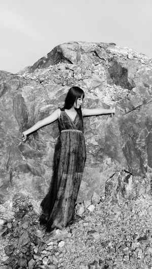 Full Length Of Woman Posing While Standing Against Rock