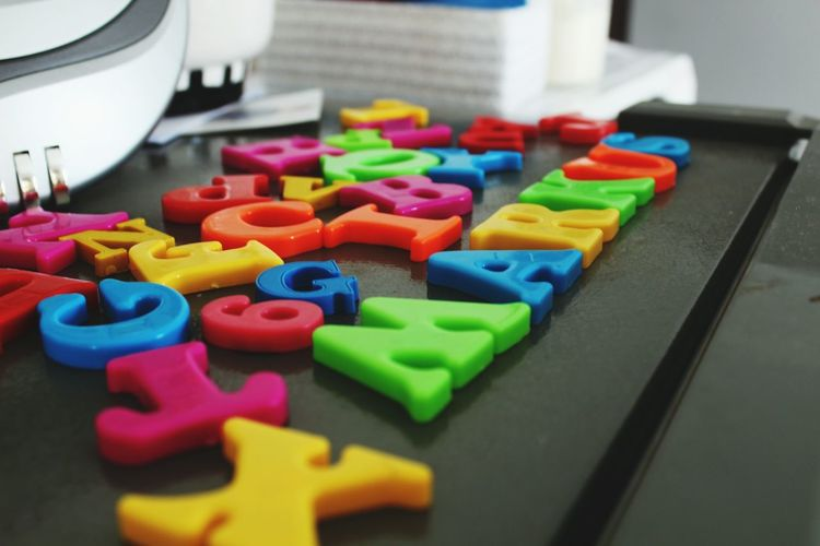 Close-up of colorful magnet alphabets on table
