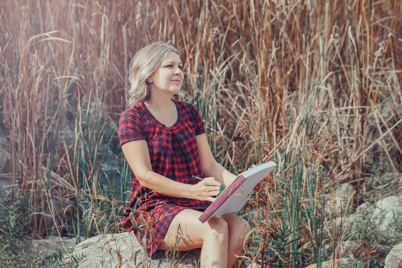 Portrait of woman sitting on grass