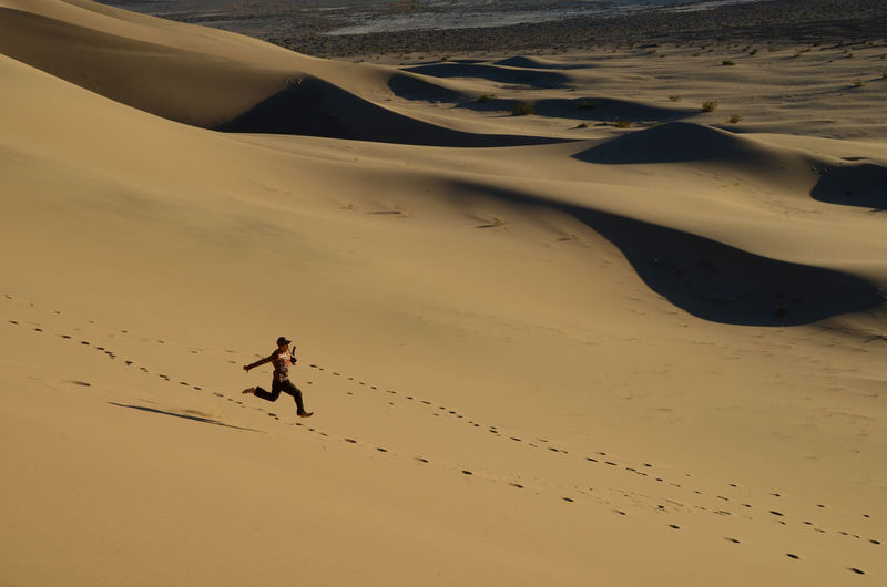 Full length of man running on sand