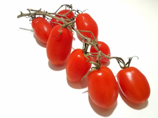 Sweet grape tomatoes on the vine Isolated Grape Tomatoes Vitamin Food Healthy Salad Organic Fresh Summer White Background Fruit Red Tomato Studio Shot Ripe Hanging Close-up Food And Drink Cherry Cherry Tomato Juicy Bunch Stem Vine
