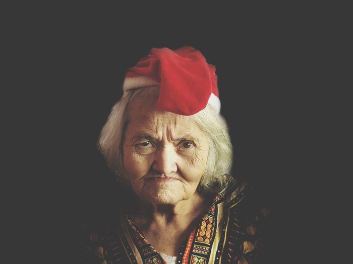 Portrait Of Senior Woman In Santa Hat Against Black Background