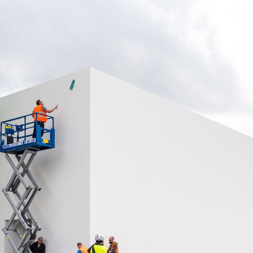 Low angle view of people on white wall against sky