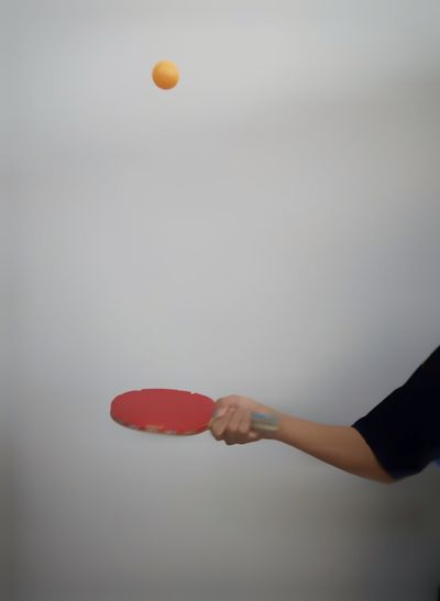 Cropped hand of woman playing table tennis against gray background