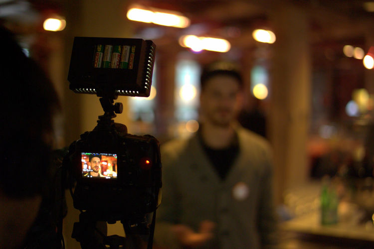 Camera filming man in illuminated restaurant