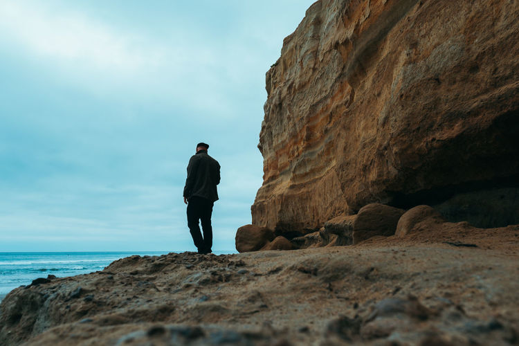 Man standing on rock against sea