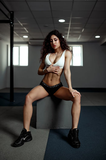 Young woman sitting on box in gym