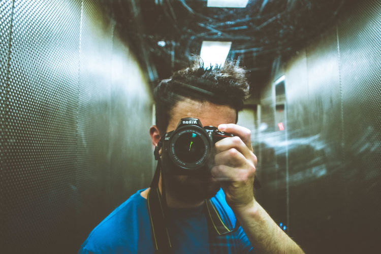 Portrait of young man photographing through camera