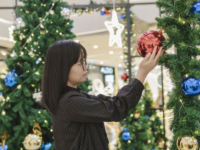 Female Holding Decoration Christmas Tree christmas tree Christmas Holiday Decoration Celebration Christmas Decoration Holiday - Event Lifestyles One Person Tree Christmas Ornament Plant Real People Standing Women Christmas Lights Focus On Foreground Hairstyle