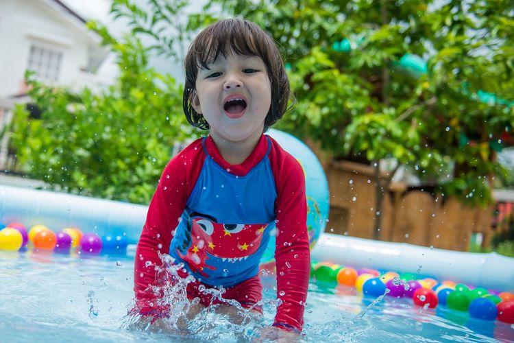 Cute girl playing in swimming pool