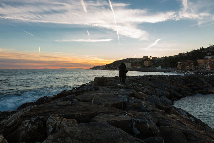 Silhouette couple standing on rocks at beach during sunset