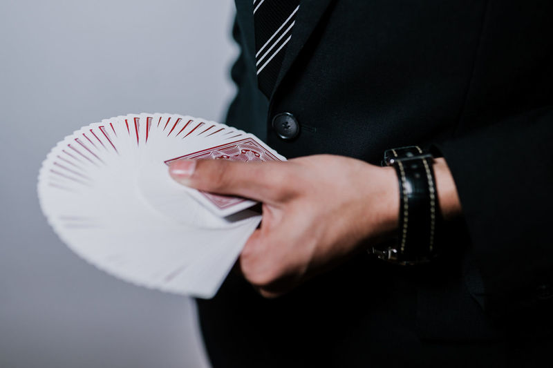 Midsection Of Man Holding Playing Cards Against Gray Background