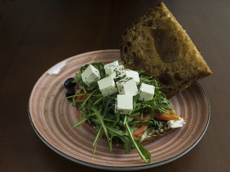 sandwich with feta cheese, tomatoes, olives, red onions and arugula Red Onions Sandwich Arugula Bread Cheese Close-up Day Directly Above Feta Food Food And Drink Freshness Green Color Healthy Eating High Angle View Indoors  No People Olives Plate Ready-to-eat Table Tomatoes