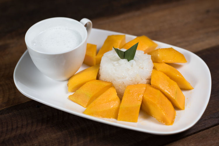 mango sticky rice or Khaoniao mamuang, a traditional thai cuisine ASIA Coconut Milk Glutinous Rice Mango Thailand Appetizer Close-up Culture Cup Food Food And Drink Fresh Mango Freshness Gastronomy Healthy Eating Khaoniao Mamuang Mango Fruit Mango Sticky Rice Plate Ready-to-eat Sticky Rice Table Temptation Thai Famous Food Wood - Material