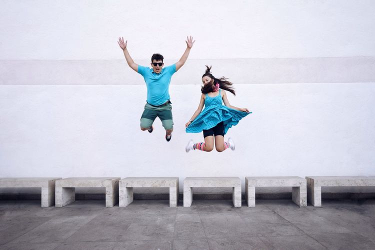 Playful friends jumping against white wall