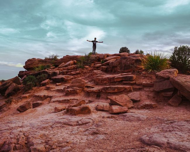 Man standing on grand canyon against cloudy sky.