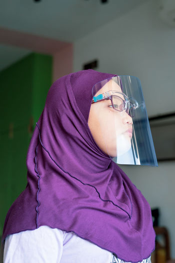 Girl in hijab wearing face mask at home
