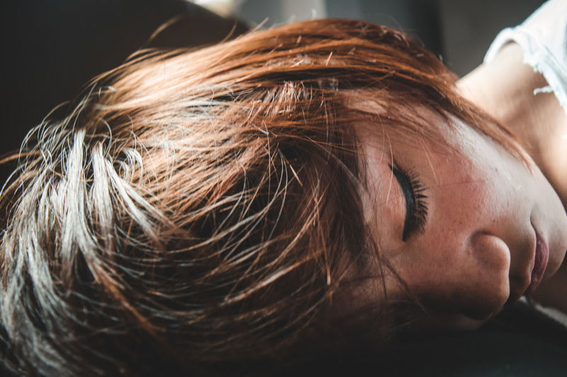 Close-up of tired woman sleeping on table