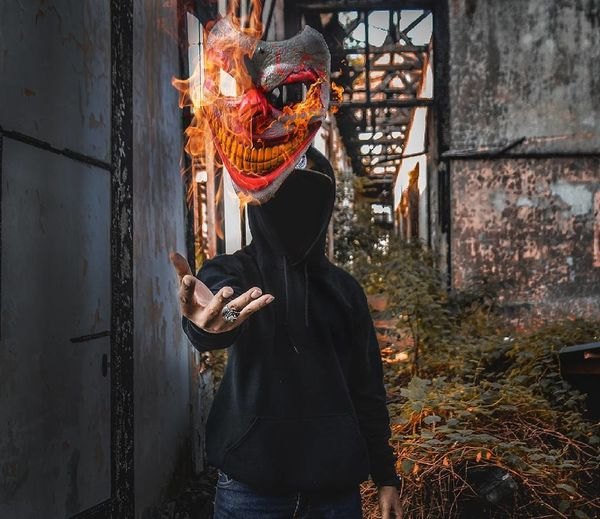 Digital Composite Image Of Person Catching Burning Mask