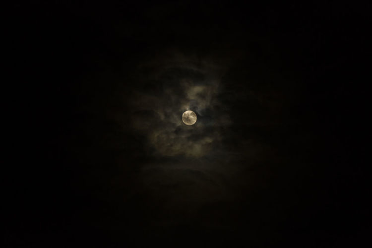 Low angle view of moon in the dark