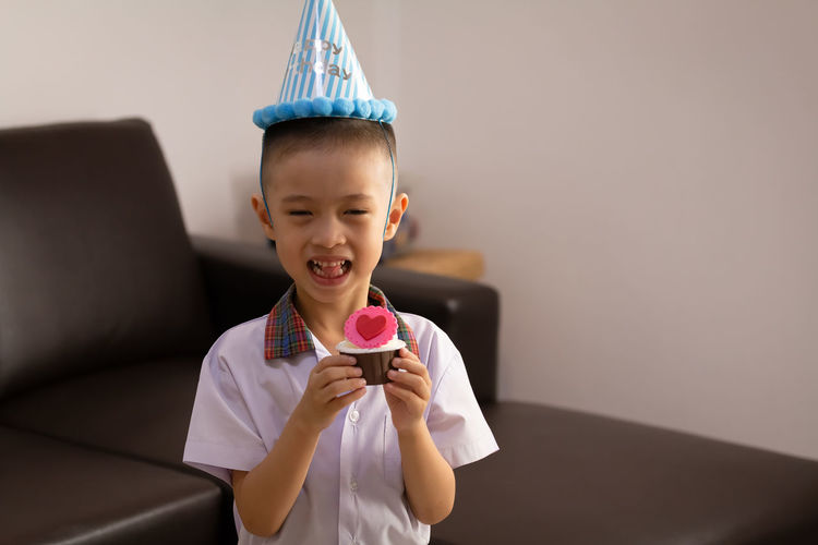 Portrait of boy holding cupcake at home