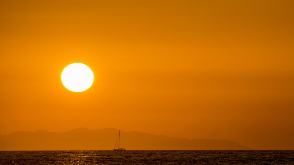 Dunst Abendstimmung Am Meer Beauty In Nature Boot Day Horizon Over Water Meerblick Mountain Nature Nautical Vessel No People Orange Color Outdoors Scenics Sea Sky Sun Sunset Tranquil Scene Tranquility Travel Destinations Water Yellow The Great Outdoors - 2018 EyeEm Awards