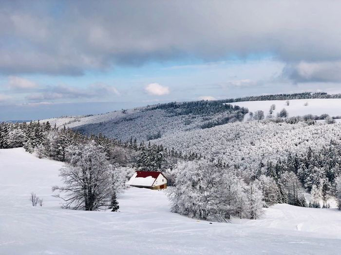 Lonely house in the mountains surrounded by forest covered in snow Tranquility WoodLand Frozen Non-urban Scene No People Isolated Wild Remote Built Structure Architecture Chalet Cabin House Mountain Range Snow Winter Cold Temperature Cloud - Sky Sky Environment Nature Mountain Landscape Beauty In Nature Scenics - Nature Tranquil Scene Outdoors Forest Tree White Color