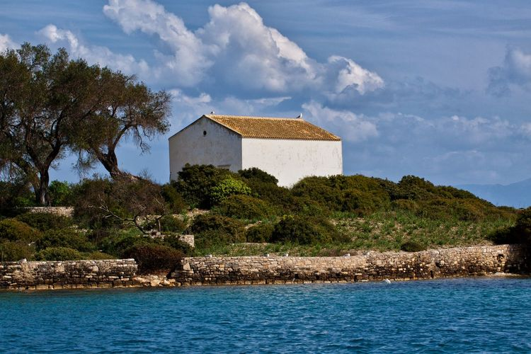 Small church at Paxos, a small island south of Corfu, Greece. Water Architecture Built Structure Tree Sky Nature No People Plant Building Building Exterior Day Outdoors Cloud - Sky Sea Tranquility Waterfront Land Beauty In Nature Church Church Architecture Churches Island Cloud Port