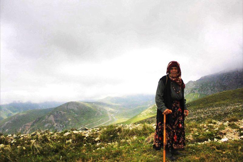 Portrait of senior woman on mountain against sky