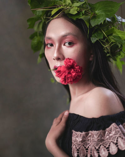 Portrait of a beautiful young woman standing by red flowering plant