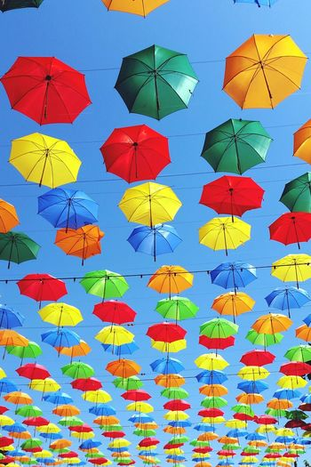 Low angle view of multi colored umbrellas hanging against clear sky