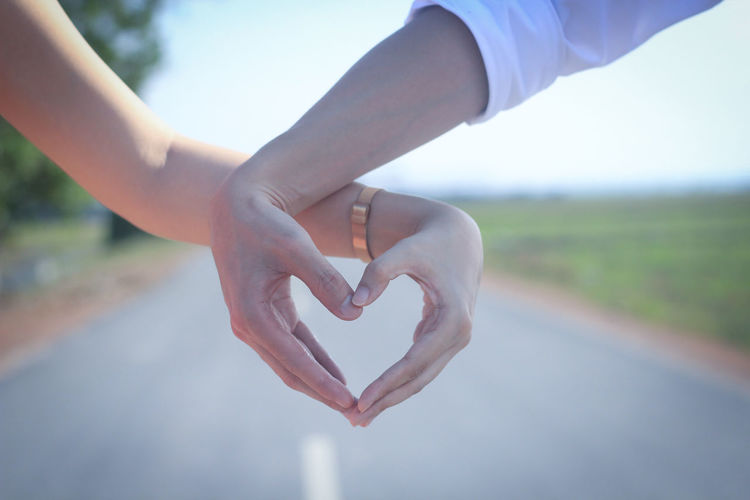 Cropped Image Of Couple Making Heart Shape On Road