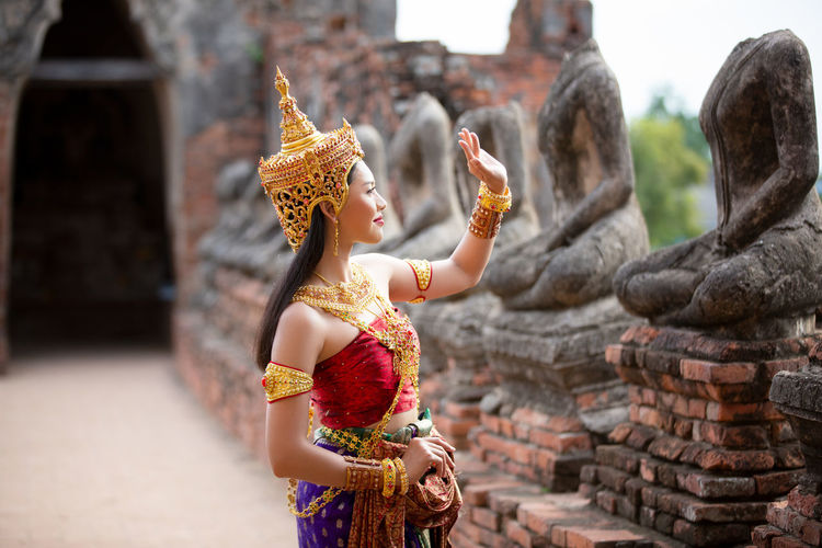 Woman in traditional clothing standing by statues at temple building