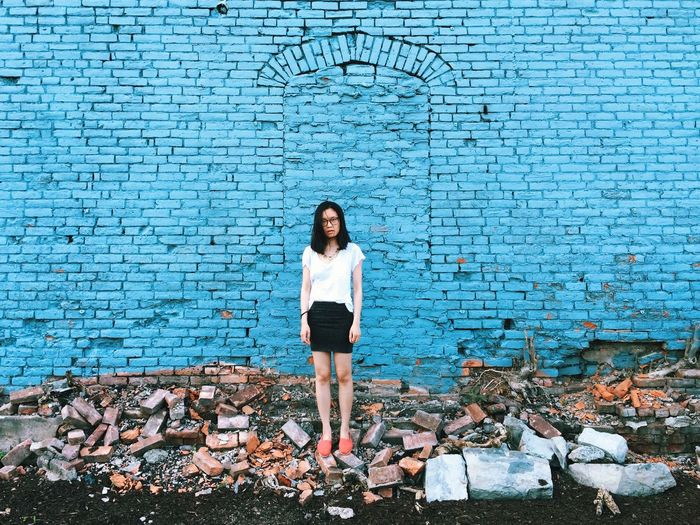 Full Length Of Woman Standing Amidst Bricks Against Blue Wall