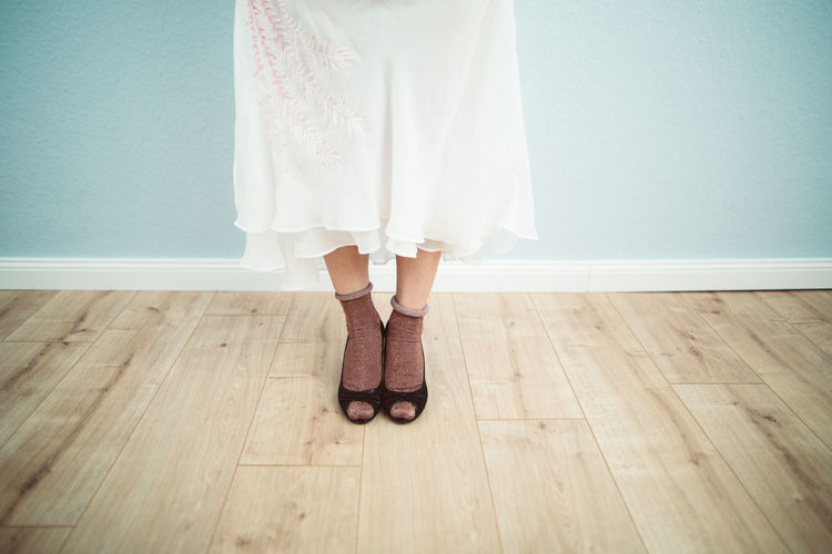 Low section of woman standing on hardwood floor