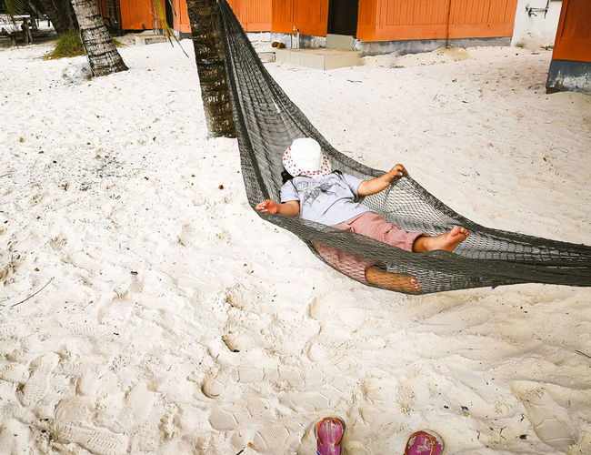One Person Real People Lying Down Leisure Activity High Angle View Day Relaxation Low Section Lifestyles Full Length Nature barefoot Land Sand Outdoors Resting Casual Clothing Human Body Part Covering Human Foot