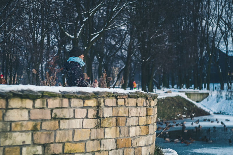 Girl standing by stone wall during winter