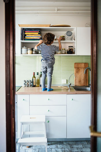 Kitchen Domestic Kitchen Rear View Home One Person Domestic Room Full Length Domestic Life Indoors  Household Equipment Standing Appliance Lifestyles Casual Clothing Real People Childhood Child Refrigerator Home Interior Cabinet Arms Raised Danger Alone Boy Preschooler